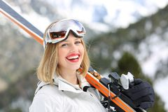 Happy skier looking at camera holding skis. In the mountain in winter holiday stock photo