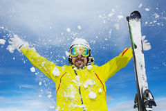 Happy skier man throw snow over sky. Man skier with beard throw snow up over blue sky wearing helmet and mask Royalty Free Stock Images