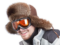Happy skier portrait. Cropped happy skier portrait of a bearded you man wearing sunglasses and a fur bearskin hat, leaning forward ready for action. Isolated Royalty Free Stock Images