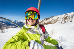 Happy skier riding to top of mountain on chairlift. Happy female skier riding up to the top of mountain on chairlift enjoying beautiful view of nature Royalty Free Stock Photos