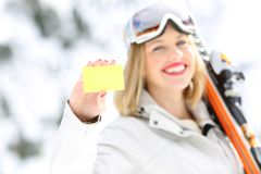 Happy skier showing a card in a slope. Front view portrait of a happy skier hand showing a card in a slope with a snowy mountain in the background Royalty Free Stock Image
