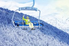 Happy skier in on the ski lift waiving hand Royalty Free Stock Image