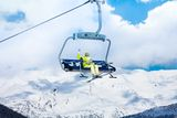Happy skier in on the ski lift. Happy skier young woman sit on the ski lift and waiving hand with mountains on background Royalty Free Stock Images