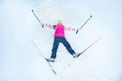 Happy skier with skis an sticks laying on the snow Royalty Free Stock Photo