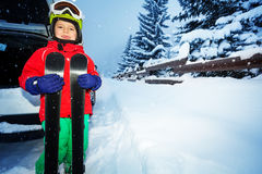 Happy skier standing next to car trunk in evening Royalty Free Stock Image