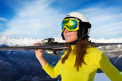 Happy skier woman on sunny day. Portrait of woman in light winter outfit ski mask and helmet holding ski over the mountain view Stock Photos