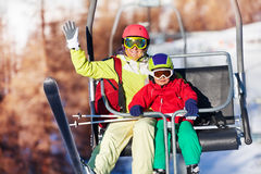 Happy skiers lifting on chairlift at mountains Stock Photography
