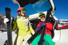 Happy skiers sitting in car trunk and holding skis Royalty Free Stock Photos