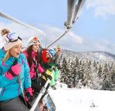 Happy skiers in ski lift lifting up on ski terrain royalty free stock photos