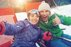 Happy skiers take a selfie photo on the top of mountain Stock Photo