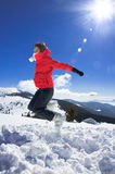 Happy skiing girl jumping in snow. Happy skiing girl jumping around and fooling in snow during a sunny day in the mountains Royalty Free Stock Photos