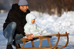 Happy sledding. Happy father and his baby boy are sledding Stock Images