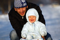 Happy sledding. Happy father and his baby boy are sledding Stock Photography