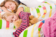 Happy sleeping. Two young children enjoying their colorful bed royalty free stock image
