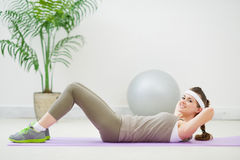 Happy slim woman doing abdominal crunch Royalty Free Stock Image