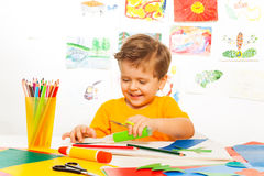 Happy small boy crafts with scissors, paper, glue Stock Images