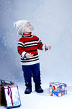 Happy small boy  in knitted hat and pullover with gift boxes. Royalty Free Stock Photography