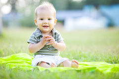 Happy small boy outdoors in a park Stock Photos