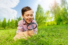 Happy small boy searches with magnifier and laying Royalty Free Stock Photography