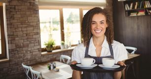Happy small business owner woman holding two coffees stock photography