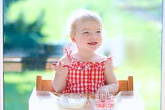 Happy small child eating yogurt with strawberries. Smiling little blonde toddler girl eating delicious yogurt sitting in the kitchen in a high feeding chair next Royalty Free Stock Photography