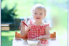 Happy small child eating yogurt with strawberries. Smiling little blonde toddler girl eating delicious yogurt sitting in the kitchen in a high feeding chair next Stock Photography