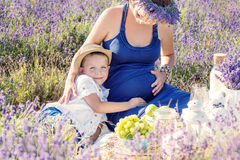 Happy small child hugs a pregnant mother Royalty Free Stock Photo