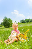 Happy small girl cuddles rabbit in green meadow Stock Photography