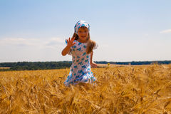 Happy small girl dancing in a field Royalty Free Stock Image