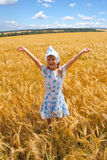 Happy small girl dancing in a field Stock Photos