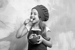 Happy small girl eating chocolate cookies dessert in cook hat. Happy small girl eating chocolate cookies dessert in red cook hat and chef apron on colorful Stock Photography