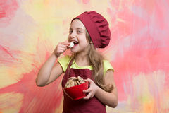 Happy small girl eating chocolate cookies dessert in cook hat Royalty Free Stock Images