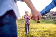A small girl with her senior grandparents having fun outside in nature. Royalty Free Stock Image
