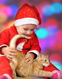 Happy small girl in santa red hat playing with kitten Royalty Free Stock Image