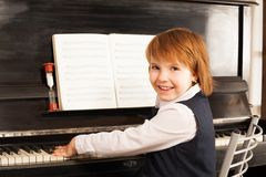Happy small girl in school uniform plays piano Stock Images