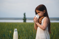 Happy small girl in a white dress drinking milk in a green field.  Royalty Free Stock Photo