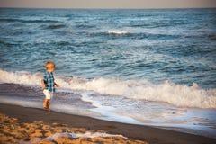 Happy small stylish boy in white shorts and blue shirt enjoying life on summer beach.  Stock Photos