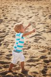 Happy small stylish boy in white shorts and striped blue t-shirt. Enjoying life on summer beach Stock Images