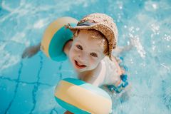 A small toddler boy with armband swimming in water on summer holiday. royalty free stock photos