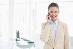 Happy smart brown haired businesswoman calling with her mobile phone Stock Photography