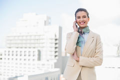 Happy smart brown haired businesswoman making a phone call Stock Photos