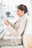 Happy smart brown haired businesswoman reading a newspaper Royalty Free Stock Photo