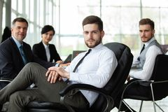 Happy smart business man with team mates discussing in the background royalty free stock images