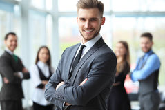 Happy smart business man with team mates discussing in the background. Stock Photos