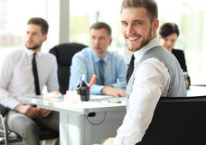 Happy smart business man with team mates discussing in the background. Royalty Free Stock Photography