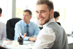 Happy smart business man with team mates discussing in the background. Stock Image