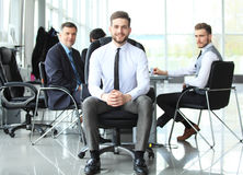 Happy smart business man with team mates discussing in the background. Royalty Free Stock Photos