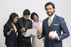 Happy smart businessman holding piggy bank with his busy colleagues. Cheerful businessman holding piggy bank with his busy colleagues on white background Stock Images