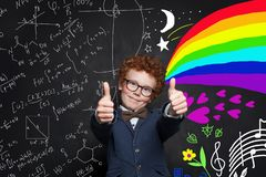 Happy smart child boy showing thumb up on blackboard background with science formula  and art pattern.  stock photography