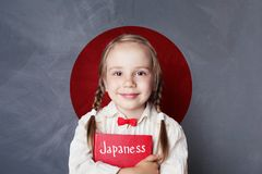 Happy smart child girl with book on Japan flag background. Learning japanese language stock photo